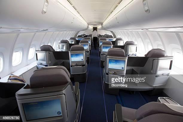 In flight entertainment screens sit on passenger seats in Deutsche Lufthansa AG's business class cabin of a Boeing 7478 passenger aircraft...