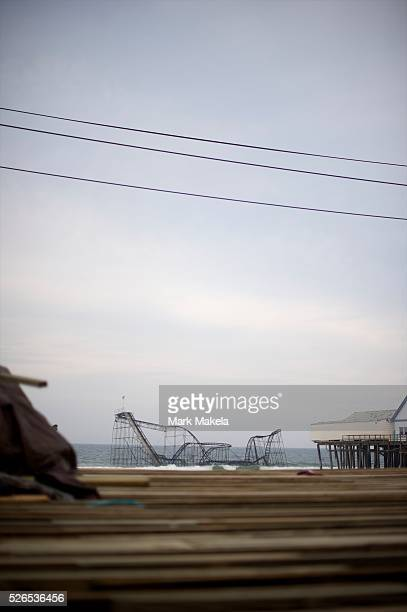 In font of the destroyed boardwalk passerbys observe and photograph the iconic roller coaster submerged in the Atlantic Ocean as a result of...
