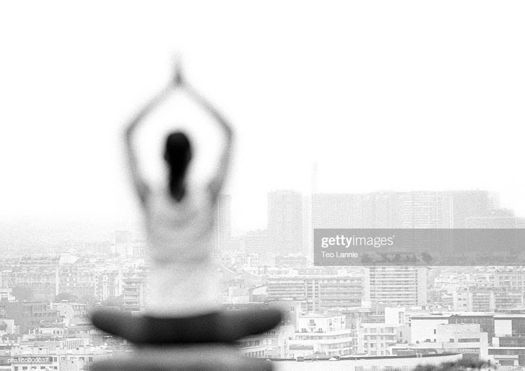 In foreground, woman practicing yoga, rear view, blurred, focus on cityscape in background, b&w : Stockfoto