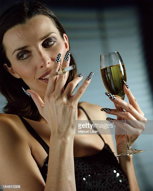 In France studio portrait of a young woman smoking a cigarette with a cigarette holder and holding a glass filled with green liquid wearing fake...