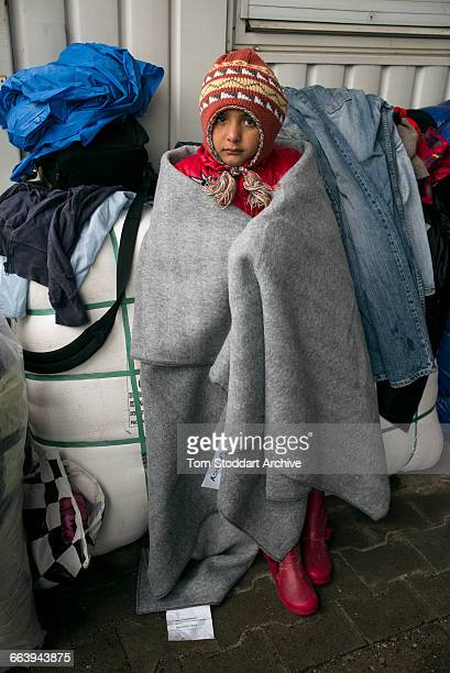In freezing cold a refugee child waits to cross at the Timovec border crossing between Croatia and Slovenia. The ICRC handed out clothes to try to...