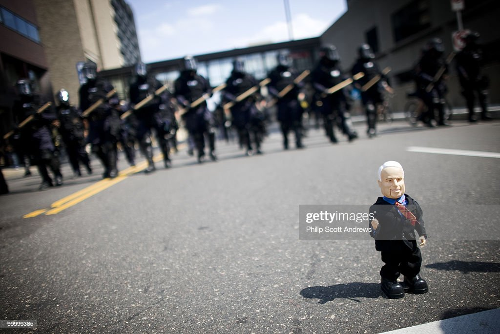 In front of a John McCain doll, Police Officers armed with batons and riot gear walk down a street during an anti-war demonstration on the first day of the RNC.