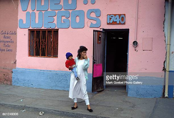 In front of a pink and blue adobe building a mother holds a boy on the street Juarez Mexico late 1980s