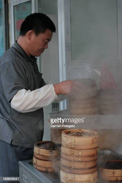 CONTENT] In front of a small restaurant a cook is holding bamboo baskets with steamed dumplings called Xiaolong Bao one of the most famous Shanghai...