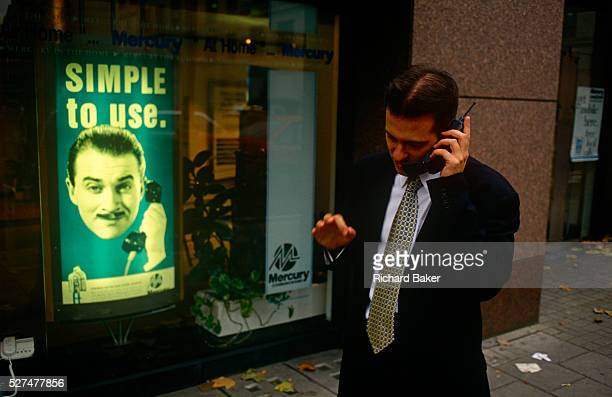 In front of an ad for Mercury, the 90s mobile phone network provider, a city worker uses his mobile phone in a London street. Actor Harry Enfield was...