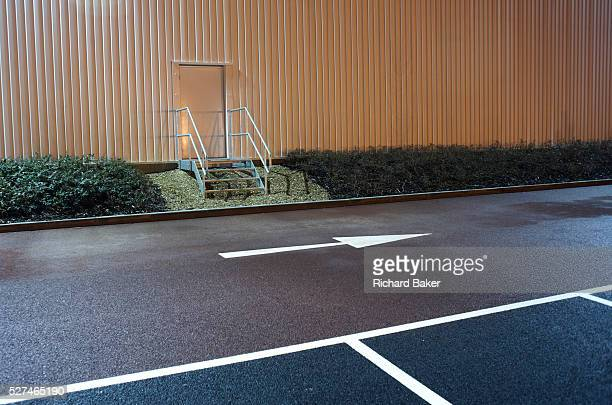 In front of an industrial doorway with a safety handrail and near empty parking bay markings a stencilled arrow points from left to right at the...