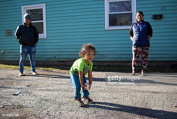 In front of his home Dipson Gurung plays with a ball Burlington Vermont December 5 2015 In the background his mother Hema Gurung watches the person...