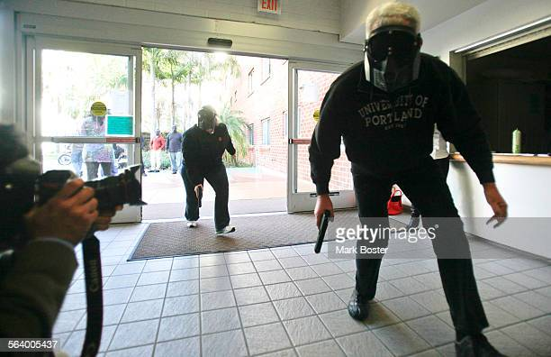 In front of media camera crews San Diego State Chaplain Dana Garrett and retired police officer Chuck Harold simulate a police team entering the...