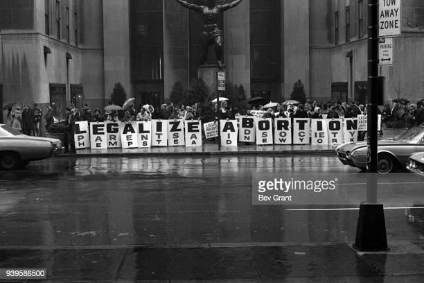 In front of the Atlas sculpture at Rockefeller Center activists hold a series of signs that read 'Legalize Abortion' during a demonstration New York...