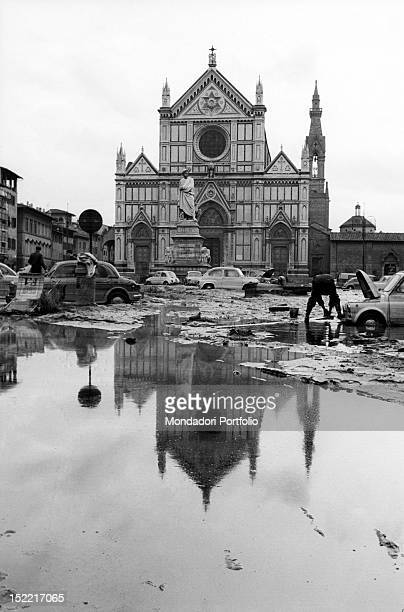 In front of the basilica of Santa Croce there are only water and cars covered in the mud left by the flood Florence 1966