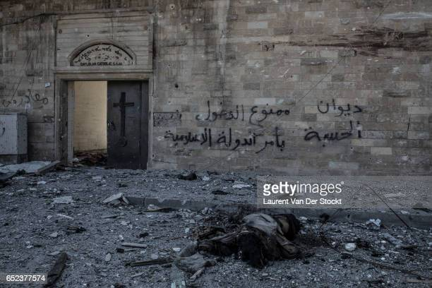 """In front of the christian chaldean church Um Al-Mahuna in west Mosul. The dead body of a IS fighter and graffiti reading """"Forbidden to enter by the..."""