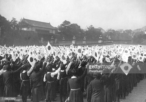In front of the Imperial Palace Japanese schoolgirls wave flags in celebration of the Japanese military victory Tokyo Japan December 15 1937 They...