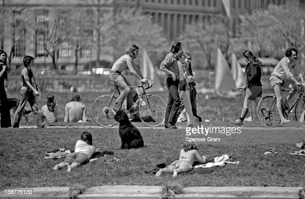 In front of the Massachusetts Institute of Technology sunbathers and pedestrians relax on the Charles River Embankment Boston Massachusetts 1971