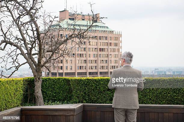 CONTENT] In front of the Velasca tower a man looks at the landscape of Milan