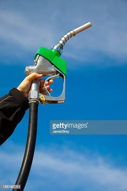 In Gas We Trust; Gasoline Pump Nozzle Held Toward Sky