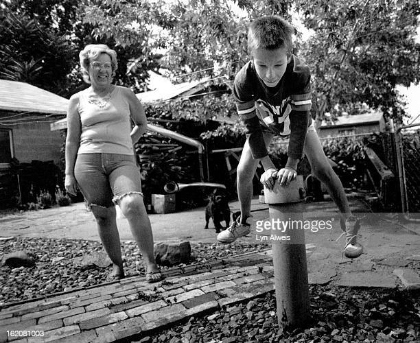 JUL 27 1989 In Globeville on East 49th Ben Oletski jumps over a ASARCO monitor well that is next to their home and garden They were connected to a...