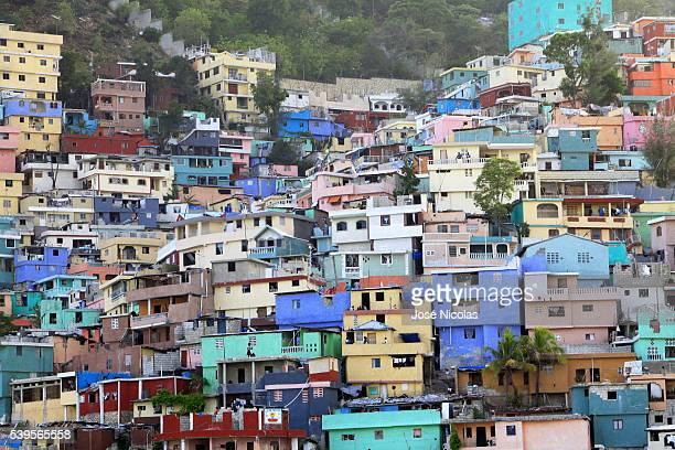 In Haiti's Jalousie slum workers have begun painting the concrete facades a rainbow of purple peach lime and cream inspired by the dazzling...