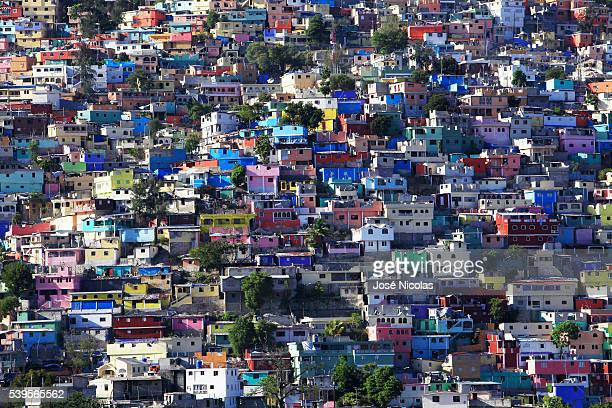 In Haiti's Jalousie slum, workers have begun painting the concrete facades a rainbow of purple, peach, lime and cream, inspired by the dazzling...