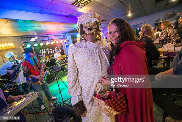 In Halloween costumes, the Big Bad Wolf and Little Miss Riding Hood pose for a photo while celebrating at the local bar The Sports Den where Whiskey...