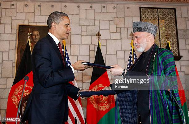 In handout image released by the Afghan Presidents Office, US President Barack Obama exchanges documents with Afghanistan President Hamid Karzai ,...