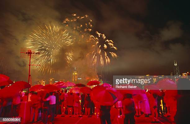 In heavy monsoon rain crowds gather at the stroke of midnight beneath umbrellas to witness the transfer of sovereignty of Hong Kong from the United...