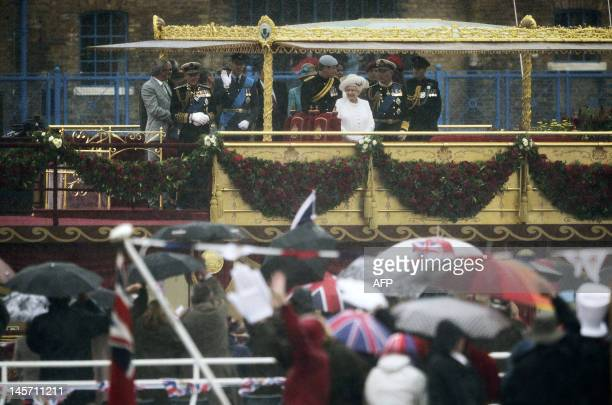 In heavy rain Prince Philip Duke of Edinburgh Prince William Prince Harry Britain's Queen Elizabeth II and Prince Charles Prince of Wales watch from...