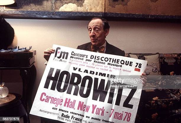 In his apartment, classical musician Vladimir Horowitz poses with a poster that advertises his Carnegie Hall performance , New York, New York, May 5,...