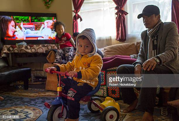 In his aunt and uncle's livingroom Sajal Gurung rides a tricycle as he is watched by his cousin Dipson and father Santa Burlington Vermont December 9...