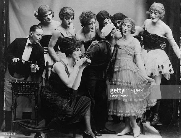 In his first stage role American actor James Cagney stands on stage with other male actors dressed in drag while a man in a sailor suit leans over to...