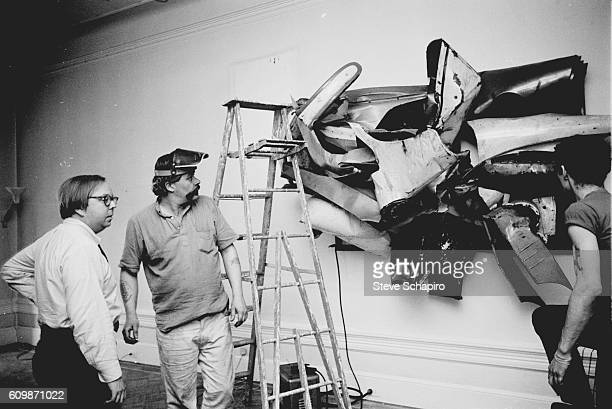 In his home art curator and historian Henry Geldzahler watches as American sculptor John Chamberlain installs one of his works on the wall New York...