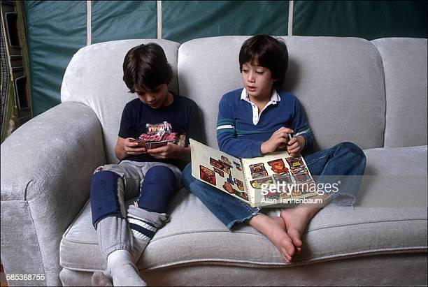 In his home at the Dakota Apartments future musician Sean Lennon and an unidentified friend sit on a couch and play with trading cards New York New...