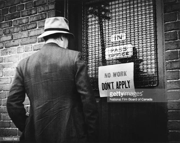 In his hopeless search for a job, a man is standing in front of a door on which there is a sign that says: 'NO WORK. DON'T APPLY', Canada, 1943....