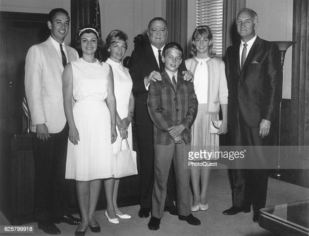 In his office FBI Director J Edgar Hoover poses with ABC sportscaster Tom Harmon his daughter actress and model Kelly Jean Harmon his wife actress...