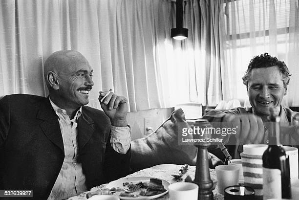 In his trailer Russianborn American Swiss actor Yul Brynner shares a laugh with an unidentified man during a meal break in the production of the film...