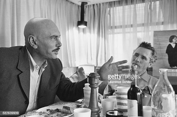 In his trailer Russianborn American Swiss actor Yul Brynner speaks with an unidentified man during a meal break in the production of the film 'Villa...