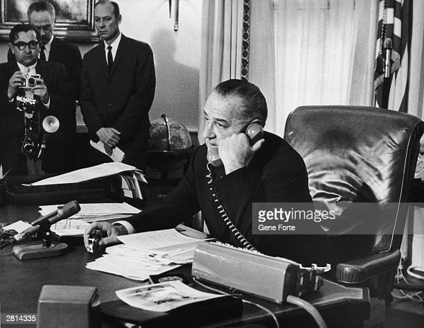 In his Washington office, US president Lyndon B. Johnson congratulates astronauts Virgil Grissom and John Young after their triple orbit of the...