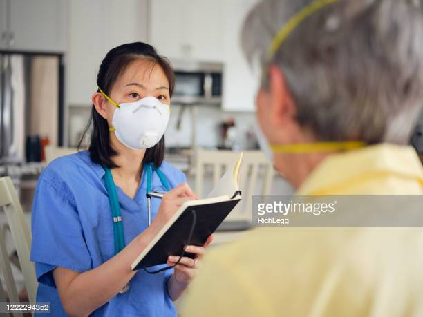 in home healthcare worker with senior aged woman - n95 face mask stock pictures, royalty-free photos & images