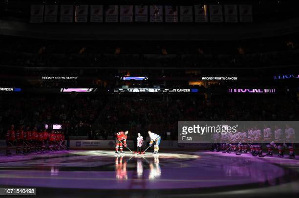 In honor of Hockey Fights Cancer night survivor Bennett Burgida drops the puck to Brian Boyle of the New Jersey Devils and Anders Lee of the New York...