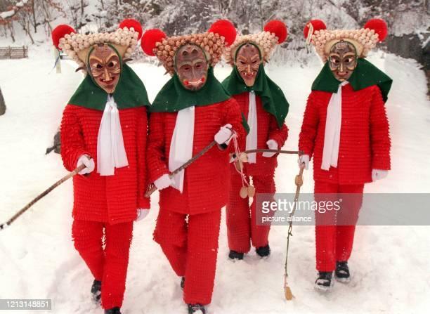 In ihren furchterregenden Holzmasken, mit rotem Zottelkleid und Dreieckshut besetzt mit Schneckenhäusern, ziehen am 10.2.1999 drei Kinder in der...