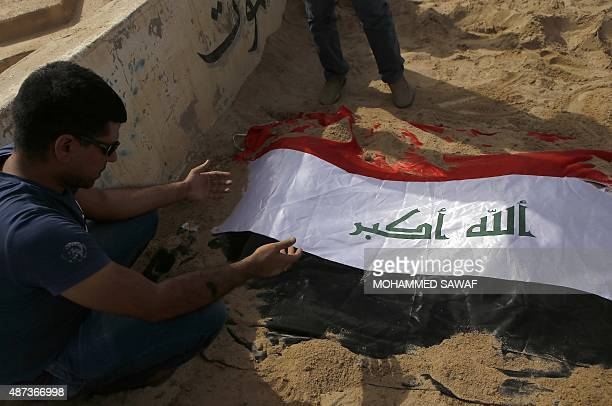 In Iraqi man prays next to the grave covered in the Iraqi flag of eightyearold boy Haidar and his 12yearold sister Zainab who drowned in a boat...