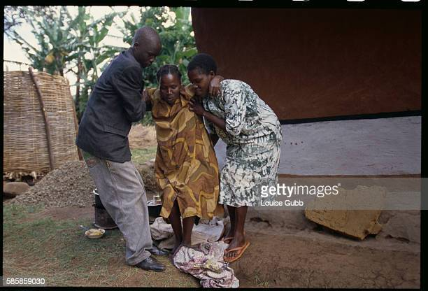 In Kapchorwa Uganda two people help a paralyzed women believed to be the result of female circumcision While a traditional rite of passage throughout...