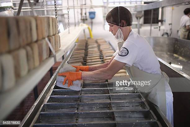 In keeping with tradition Justin Koch places bricks on Brick cheese forms to make blocks of the cheese at the Widmer's Cheese Cellars on June 27 2016...