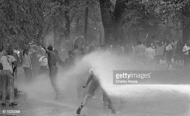 In Kelly Ingram Park an antisegregation demonstrator is knocked down by the water from a firehose Birmingham Alabama early May 1963 Police officers...
