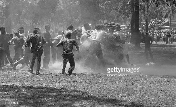 In Kelly Ingram Park antisegregation demonstrators are knocked down by the water from a firehose Birmingham Alabama early May 1963 Police officers...