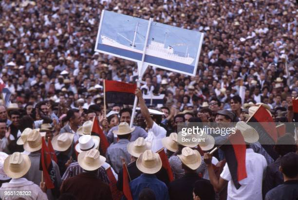 In la Plaza de la Revolucion during the 10th anniversary celebration of the Cuban Revolution a man holds up a sign that features an illustration of...