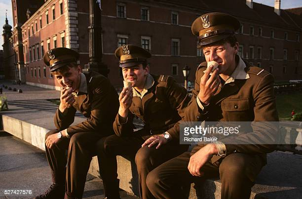 In late afternoon three conscript soldiers of the Polish army are dressed in brown uniforms eating ice cream cones in Plac Zamkowy outside the Royal...