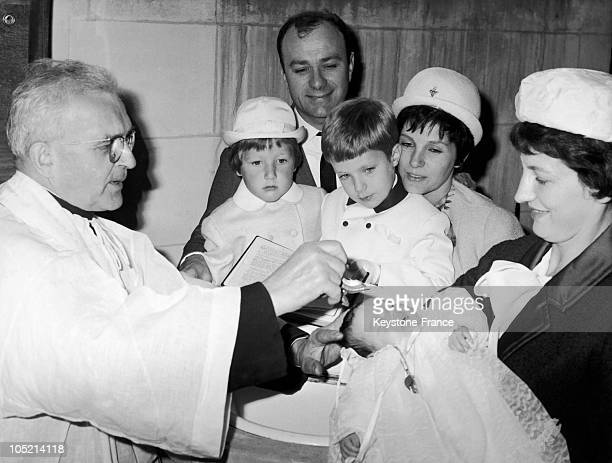 In L'EtangLaVille The Actor And Comedian Fernand Reynaud Is Moved Watching The Baptism Of His Daughter Francoise Surrounded By His Wife Renee And His...
