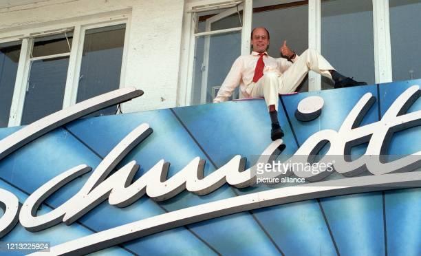 """In luftiger Höhe posiert """"Schmidt""""-Gründer Corny Littmann am 3.8.1998 auf dem Schriftzug seines Theaters an der Reeperbahn in Hamburg. Das plüschige..."""