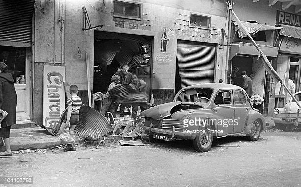 In March 1962 in Algiers inhabitants sweep out the rubble of a garage destroyed by a bomb explosion attributed to the SAO On the eve of the Evian...