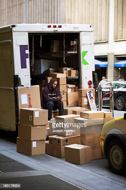 CONTENT] In March 2012 a FedEx deliveryman in midtown Manhattan taking a break in the rear of his delivery truck is surrounded by a pile of boxes to...